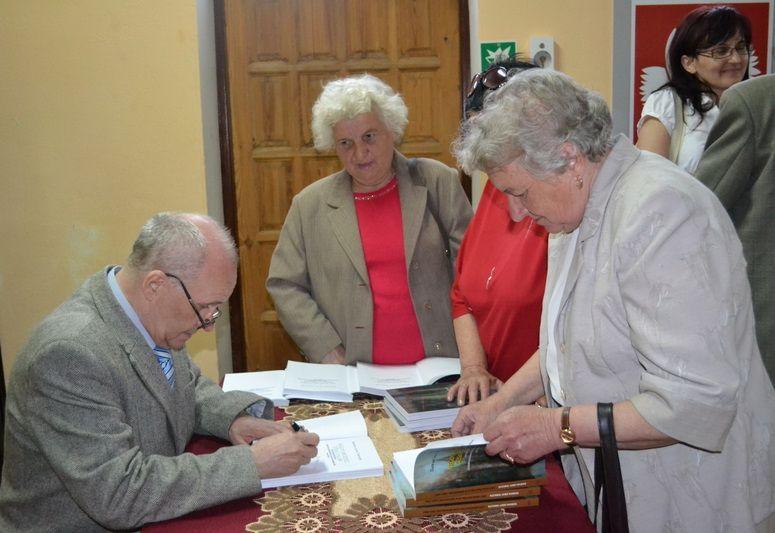autor podpisujący swoją ksiązkę podczas promocji.jpeg